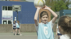 4K Young school netball team playing a match on outdoor court Stock Footage