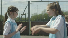 4K Young school netball teams on outdoor court high five at end of the match Stock Footage