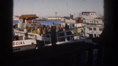 1962: a large boat filled with people docked on the water in a harbor Stock Footage