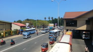 Srilankan street with buses, tuk tuks, motorcycle riders, people crossing street Stock Footage
