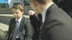 4K Young school boys chatting together outdoors in school yard Stock Footage