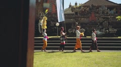 Balinese procession going to temple with offerings, umbrella and white flag Stock Footage
