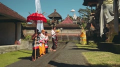 Balinese procession in temple with offerings, umbrella and white flag Stock Footage