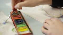 4K Close up on hand of teen girl painting a picture in school art class Stock Footage