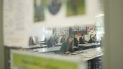 4K View through glass door of teens working at their desks in school art class Stock Footage
