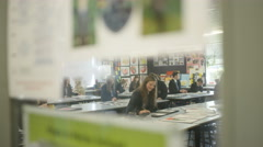 4K View through glass door of teens working at their desks in school art class Stock Footage