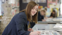 4K Portrait smiling teen girl working on a project in school art class Stock Footage