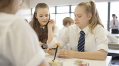 4K Children in school cafeteria at break time, eating healthy lunches & chatting Stock Footage