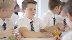 4K Young boys in school cafe at break time, eating healthy lunches & chatting Stock Footage