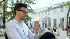 Man chatting on loudspeaker in the outdoor cafe and smiling to the camera Stock Footage