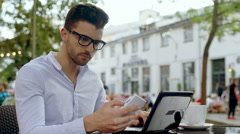 Man checking outcomes and looking irritated while sitting in the outdoor cafe Stock Footage