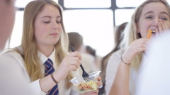 4K Young girls in school cafe at break time, eating healthy lunches & chatting Stock Footage