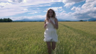 Slow motion - Front view of young female in adress running in the field of wheat Stock Footage