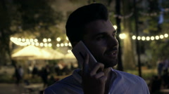 Man talking on cellphone while standing outdoors at night, steadycam shot Stock Footage