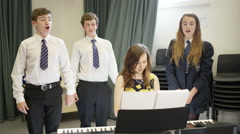 4K Teen group singing & teacher playing keyboard in school music lesson Stock Footage