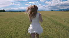 Slow motion - Back view of young female in a dress running in the wheat field Stock Footage