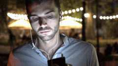 Handsome man connects earphones to smartphone and listening music, steadycam sho Stock Footage