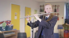 4K Teen girl playing the flute in school music lesson Stock Footage