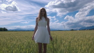 Portrait of a young woman in white dress standing in the field of wheat Stock Footage