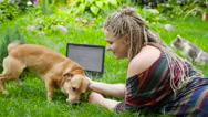 Teenager playing with a dog on the grass. HD Stock Footage