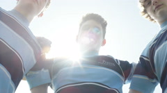 4K Teen boys in a huddle on school sports field put all hands together Stock Footage