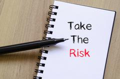 Take the risk text concept on notebook Stock Photos