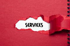 The word services appearing behind torn paper Stock Photos