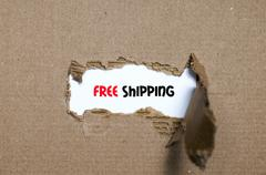 The word free shipping appearing behind torn paper Stock Photos