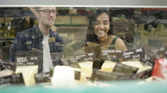 4K Couple shopping at supermarket cheese counter, looking into display cabinet Stock Footage