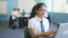 4K Portrait smiling school girl working on laptop in classroom Stock Footage