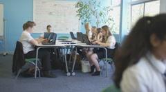 4K School children working on computers in class & getting help from teacher Stock Footage