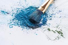 Blue, purple, green eyeshadow scattered on white background Stock Photos
