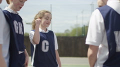 4K Young netball team at beginning of game put all hands together & give high fi Stock Footage