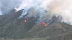 The High Park fire in Colorado burns across a mountainside as firefighters look Stock Footage