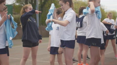 4K 2 Young netball teams on outdoor court putting on bibs at beginning of a game Stock Footage