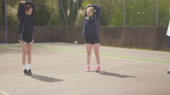 4K Young netball team on outdoor court warming up before a game Stock Footage