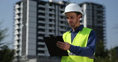 Engineer Man Working with Clipboard Looking Under Construction Building Site Day Stock Footage