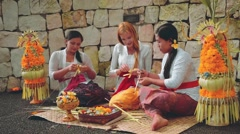 Balinese women showing caucasian woman how to make offerings Stock Footage