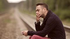 Man smokes on the rails. Stock Footage