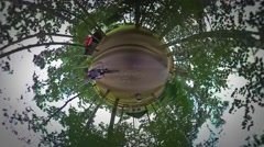 Little Tiny Planet 360 Degree Man Riding a Bike Gets Off and Walking Along Stock Footage