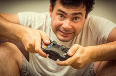 Emotional young addicted man playing video games in living room Kuvituskuvat