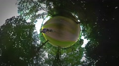Little Tiny Planet 360 Degree Man Riding a Bike by Footpath Along River Sea Stock Footage