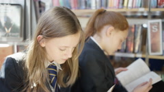 4K Young students reading books & chatting in school library Stock Footage