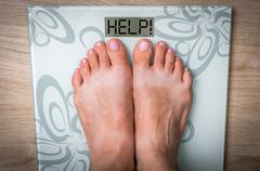 Woman's feet on a scale with word HELP! - obesity concept Stock Photos