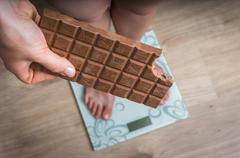 Overweight woman standing on scale and holding chocolate - obesity concept Stock Photos