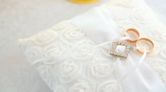 Wedding golden rings on traditional white pillow ready for wedding ceremony Stock Footage