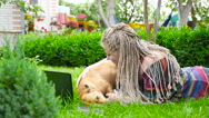 Beautiful girl lies on the grass and plays with dog. HD Stock Footage