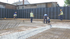 Construction workers connecting reinforcing mesh, pan right by Sheyno. Stock Footage