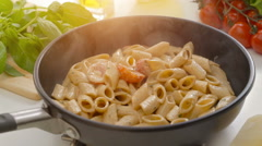 Hot penne pasta with tomato sauce in a frying pan with steam Stock Footage
