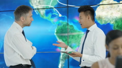 4K Businessmen talking & looking at large world map graphic. Global business. Stock Footage